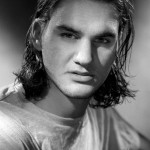 Roger Federer with long hair that is wavy and of shoulder length hairstyle