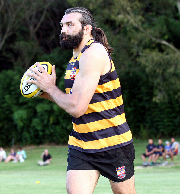 Sebastien Chabal playing rugby with long hair and a tied hairstyle for his wavy locks
