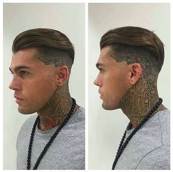 A barbershop picture of a guy with an undercut haircut and slicked back hair covering his tattoos