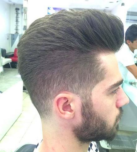 A barbershop picture of a male with a pompadour hairstyle and a short taper haircut done with a hair clipper