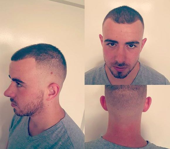 A hair salon picture of a white guy with a sharp fade haircut on the sides and back of his head