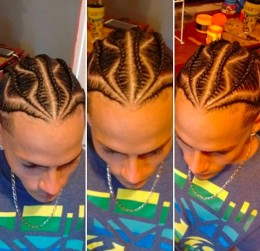 A hair salon photograph of a mixed-race guy with long cornrows braided to skin by a professional barber