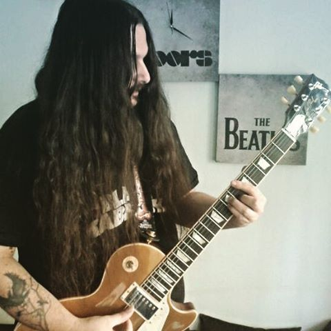 A photo of a metal-head guy with long wavy hair reaching his navel as he posed for the camera while playing heavy-metal music with his expensive guitar