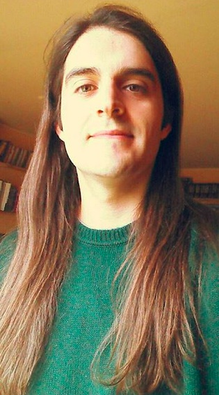 A photograph of a long-haired guy with a middle-part hairstyle as his long mane reaches his chest in length