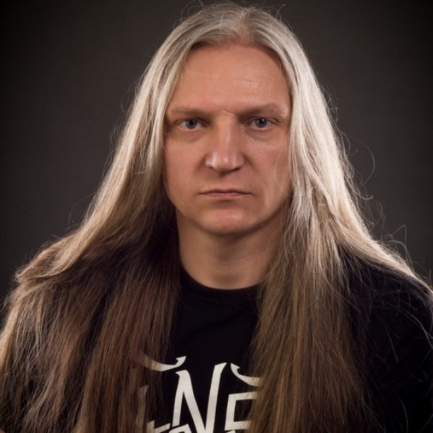 A photograph of a old white male with gray long hair styled down and straightened with a flat iron