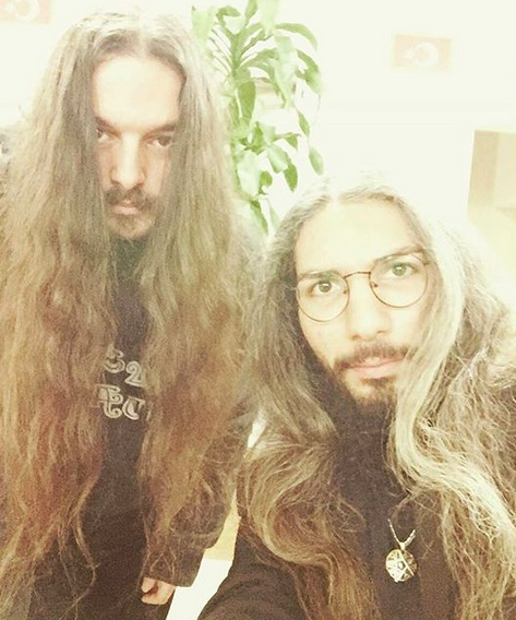 A photograph of two male members of a rock band who have very long wavy hair and Van Dyke beard styles
