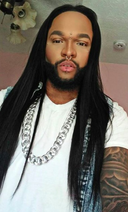 A picture of an African-American male with long straight hair which he styled across the center of his head with a hair straightener