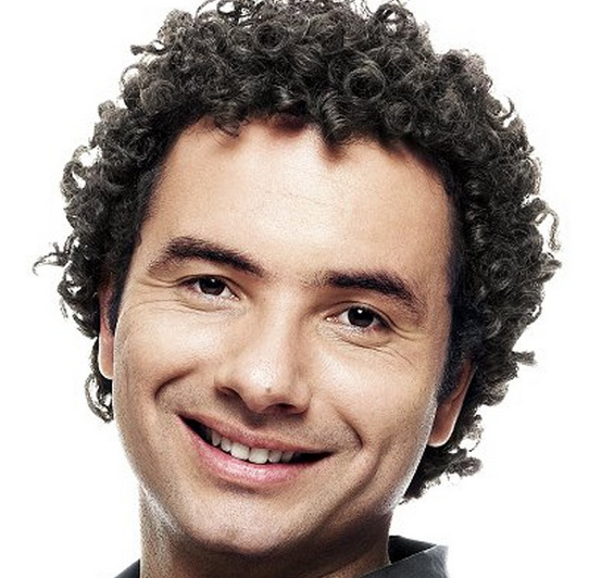 A photograph of a middle-aged white male with his medium curly hair combed back into a Jewfro hairstyle