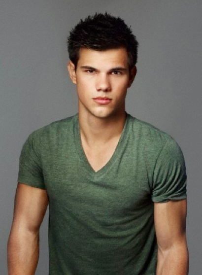 A photograph of actor Taylor Lautner with his trademarked spiky hairstyle as he poses in front of the camera with a green t-shirt