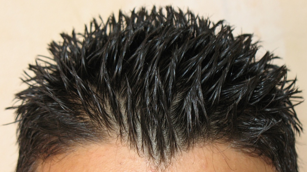 A man with a spiky hairstyle displaying brushed up hair and styled with hair gel
