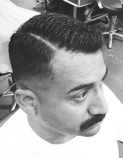 A barbershop photo of a male sporting a mustache and with side part hair cut with an executive contour haircut