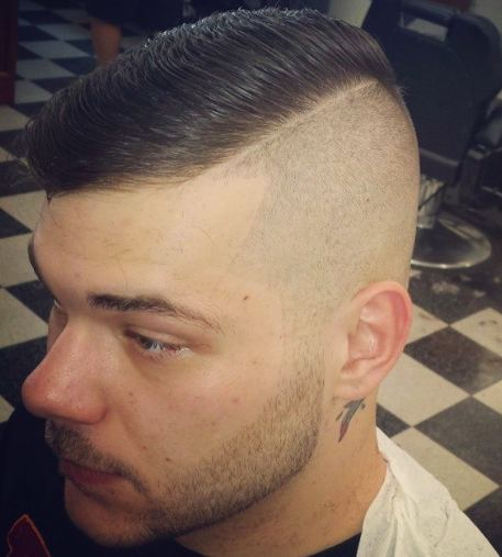 A picture at a barbershop of a guy with side parted hair in a cool disconnected haircut