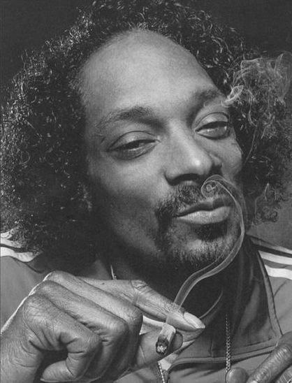 A photograph of Snoop Dogg showing his afro hairstyle with a receded hairline caused by traction alopecia from years of wearing cornrows