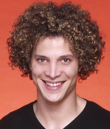 A photograph of Justin Guarini with his medium curly hairstyle as he smiles while posing for the camera during a somewhat-recent photoshoot
